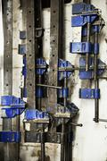 Close up of a selection of metal clamps in a carpentry workshop. Stock Photos