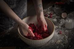 Valentine's Day baking, woman preparing fresh raspberries in a bowl. Stock Photos