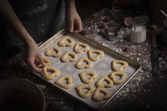 Woman arranging heart shaped biscuits on a baking tray Stock Photos