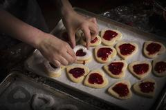Valentine's Day baking, woman spreading raspberry jam on heart shaped biscuit Stock Photos