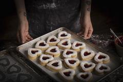 A tray of baked heart shaped biscuits Stock Photos