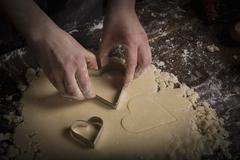 Valentine's Day baking, woman cutting out heart shaped biscuits from dough. Stock Photos