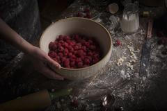 Valentine's Day baking. A bowl of fresh raspberries on a floury table. Stock Photos