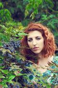 Redhead girl next to poisonous berries Stock Photos