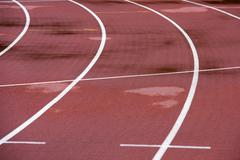 red running athletic track bad weather, wet - stock photo