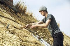 Young man thatching a roof, standing on a ladder. Stock Photos