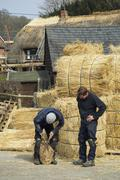 Two thatchers, one cutting a yelm of straw with a pair of shears. Stock Photos