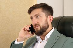 Portrait of a successful business man with mobile phone in office Stock Photos