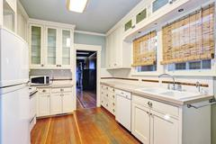 White empty simple old kitchen room with pastel blue ceiling  and hardwood fl Stock Photos