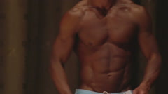 Strong male bodybuilder posing at competition, showing ideal ripped six-pack abs Stock Footage