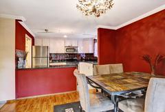 Dining area connected to kitchen with red walls, hardwood floor and vintage c - stock photo