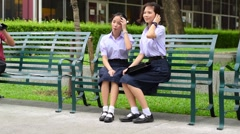 Thai high schoolgirls student couple in uniform sitting on a bench wind blowing Stock Footage