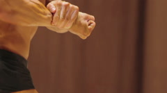 Bodybuilder demonstrating strong body in side chest and rear double bicep poses Stock Footage