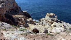 Sea laps rock below Algarve coast - stock footage