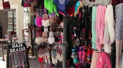 Hair braids, scarves and handbags outside a shop in a tourist street Stock Footage