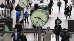 Commuters walking past clocks, Canary Wharf, London, UK Stock Footage
