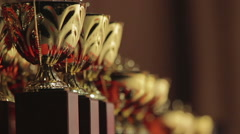 Lineup of golden cups for competition leaders, winner trophy, successful result Stock Footage