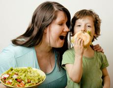 mature woman holding salad and little cute boy with hamburger teasing close up - stock photo