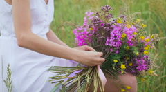 One young woman sitting on green field and winding a flower bunch Stock Footage