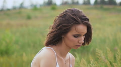 One young woman si on green field with flower bunch Stock Footage