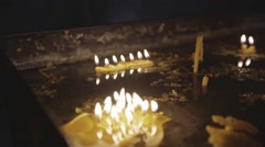 Wax church candles burning in dark rustic candlestick Stock Footage