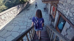 Young female walking down the stairs in Old Dilijan Complex in Armenia Stock Footage