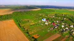 Flying over the farmland with ploughed cultivated fields and village Stock Footage
