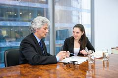 Mature businessman and young business woman discussing - stock photo