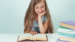 Close up portrait happy schoolgirl 7-8 years old reading book on the table Stock Footage