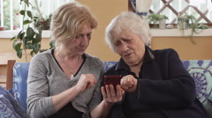 Daughter explains to her old mother how works smart phone Stock Footage