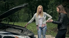 Lovely girls argue in front of broken down car - stock footage