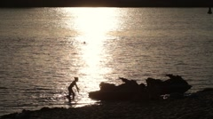 Silhouette jet ski on seashore in yellow sunset Stock Footage