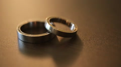 Two golden rings on brown background Stock Footage