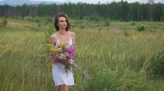 One young woman walking on green field enjoying a flower bunch Stock Footage