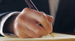 Closeup of business man hand writing in legal notebook with pen - stock footage