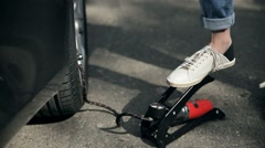 Closeup woman's foot inflating car tyre with pump Stock Footage