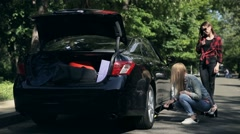 Young woman fixing flat tyre with jack on road Stock Footage