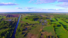 Drone flight over the farmland with irrigation channel at sunny day Stock Footage