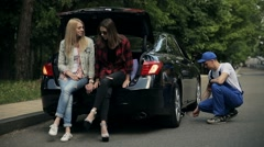 Girls sitting on trunk while mechanic fixes car Stock Footage