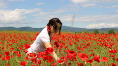 Young woman enjoying red poppy flower fragrance in blossom spring field Stock Footage