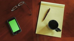 Overhead of man at desk with cell phone with green screen drinking coffee Stock Footage
