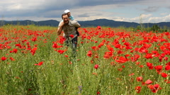 Father giving s piggy ride to his baby son in red poppies field Stock Footage