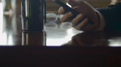 Man scrolls through his smart phone while in a coffee house at night - stock footage