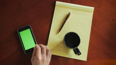 Overhead of man using mobile phone with green screen while working at desk Stock Footage