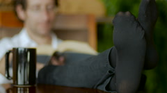 Man relaxes with feet on table reading a book and drinking coffee Stock Footage