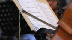 Hand playing to cello, inpiring fom notebook with musical notes from stand Stock Footage