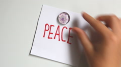 Hand put word Peace and than word War on white wall Stock Footage