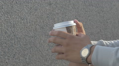 A young man on the street drinking coffee, coarsely porter Stock Footage