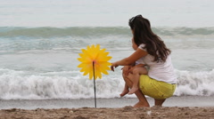 Young mother with a baby in her arms at the seaside admiring nature, hand mill Stock Footage