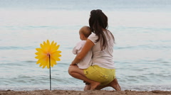 Mother and baby son on seaside, hand mill flower Stock Footage